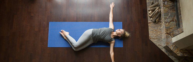 A woman does a supine twist on a yoga mat.