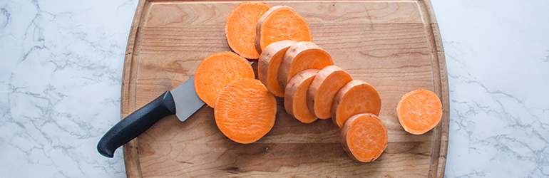 Chopped sweet potato on a cutting board.