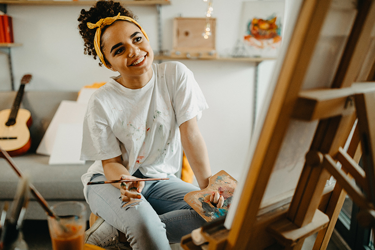 Woman smiling and painting while sitting.