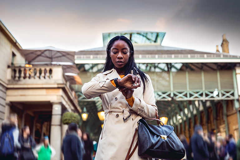 A woman stands looking at her watch in a busy market, she is wearing a tan trench coat.