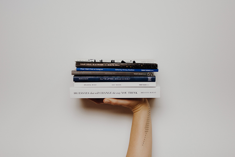 A person holds a stack of 4 white and blue books up into the frame against a white wall.