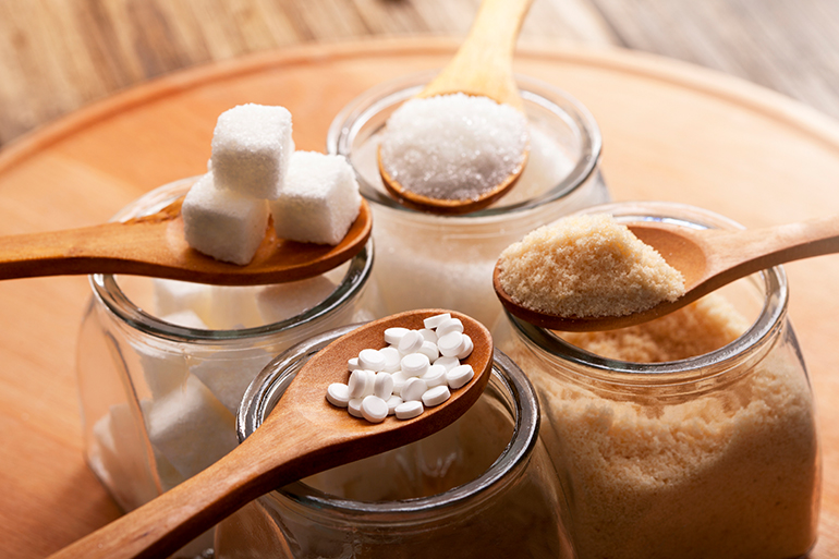 Four spoons are held within frame, each with a different type of sugar on it: sugar cubes, regular sugar, powdered sugar, and brown sugar.