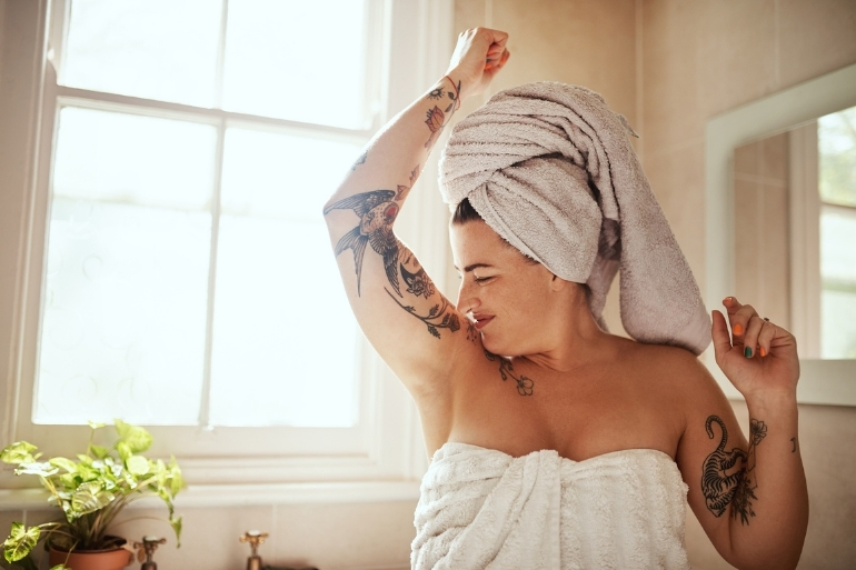 A woman sniffs her armpit after getting out of the shower.