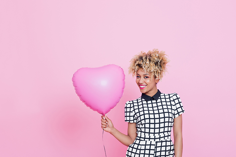 woman holding pink balloon in front of pink wall