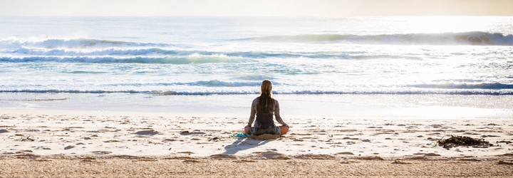 A person meditating on the beach. She is in the water and sitting facing out towards the ocean.
