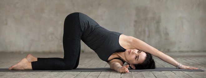 A person in thread the needle pose on a yoga mat.