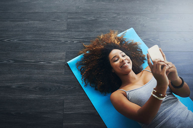 woman laying on yoga mat looking at her phone smiling