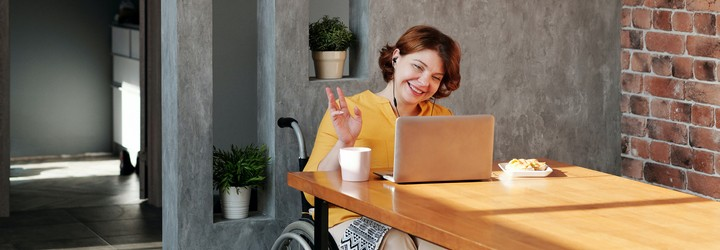 A woman in a wheelchair wearing a yellow cardigan and a white skirt is waving at the interviewer during her online interview.