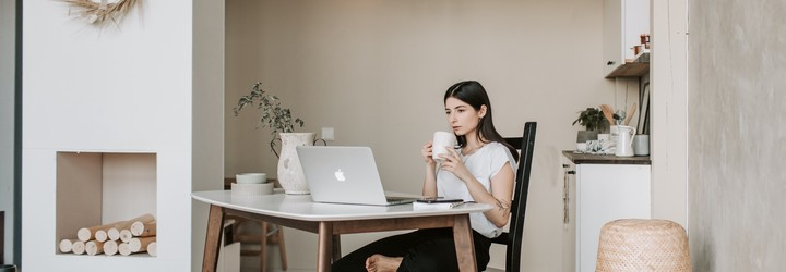A woman prepping for her online interview with a beautiful background set up filled with light and flowers.