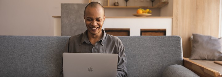 A man is sitting on his couch in a dress shirt on his laptop. He has earpods in and is smiling at the screen.