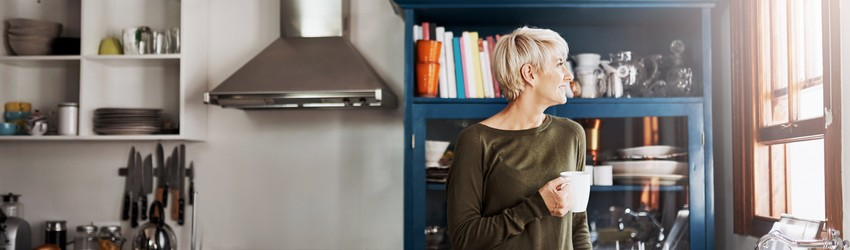 Blonde woman standing and drinking coffee in a modern blue kitchen while looking out the window which is to the left of the image.
