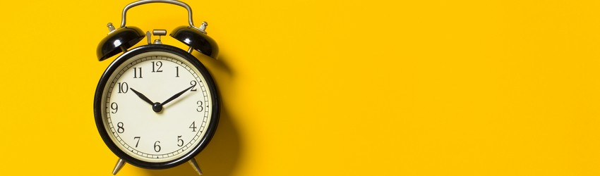 A traditional brass alarm clock on a bright yellow background.