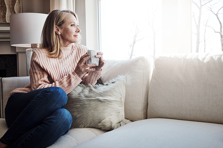 A woman sitting on a white couch looking out her window. She is holding a coffee cup.