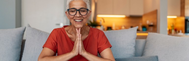 A woman smiling and meditating.