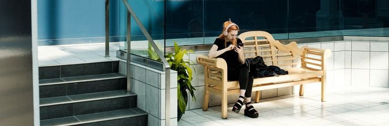 red-headed woman on a bench in a shopping mall. She is on her phone and listening to music.
