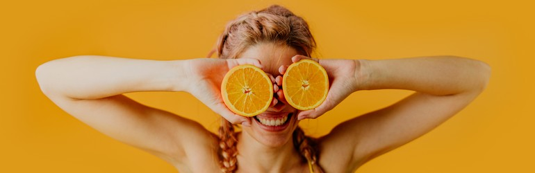 A woman smiling with oranges in front of her eyes.