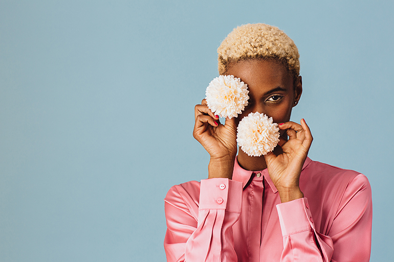 A black human with short blonde hair hides one eye and peaks out from behind two white flowers.