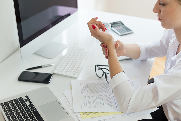 woman with wrist pain at work desk