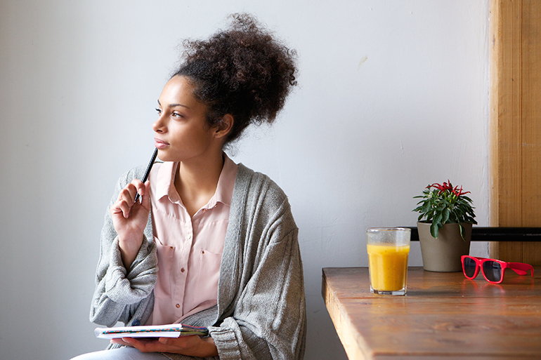 A woman ponders while writing in her journal and drinking orange juice.