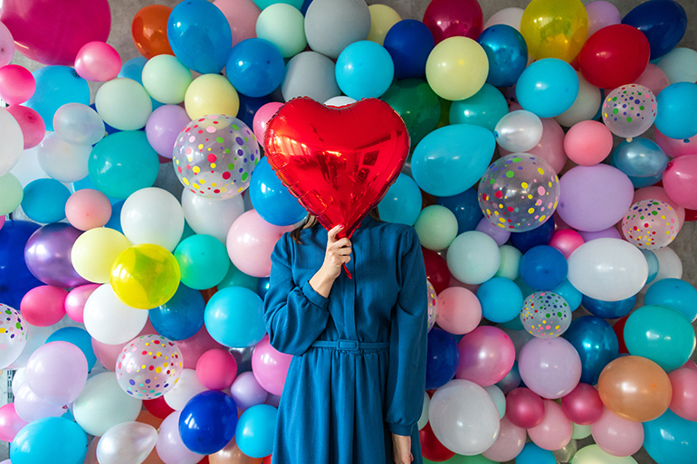 Person holding a red heart balloon in front of their face stands in front of a wall of multicolored regular balloons. They are wearing a blue denim dress.