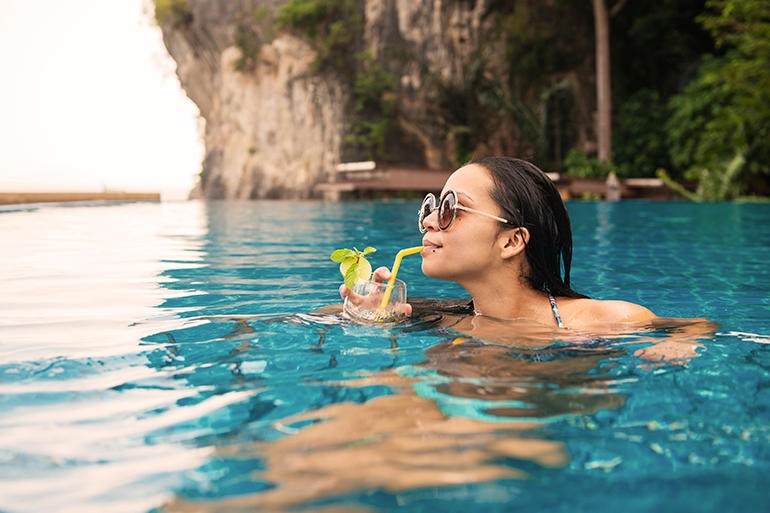 woman in swimming pool drinking water