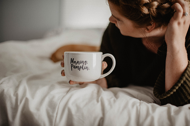 "A woman drinks coffee out of a hug that says ""morning sunshine"" on it."
