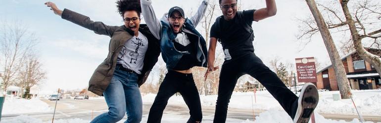 Three friends jump in excitement.